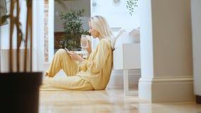Mulher loura nova que datilografa no telefone ao sentar-se em um assoalho filme