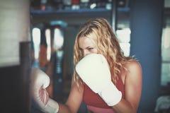 Mulher loura nova que encaixota ao saco pesado no gym cinemático Imagens de Stock