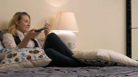 Mulher loura nova que encontra-se na cama, usando o smartphone e olhando a tevê fotos de stock