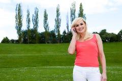 Mulher loura nova que fala sobre o telefone Imagens de Stock