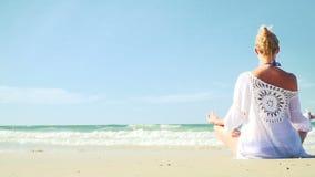 Mulher loura nova que faz a ioga na praia