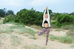 Mulher loura nova que faz a prática da ioga da manhã fora no b foto de stock royalty free