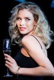 Mulher loura nova que guarda o vidro do champanhe e que olha afastado Imagem de Stock