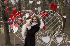 Mulher loura nova que joga com o cão na rua Foto de Stock Royalty Free