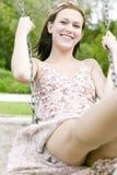 A mulher loura nova que joga em um balanço ajustou-se no parque fotos de stock