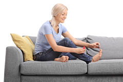 Mulher loura nova que lustra suas unhas do pé Imagem de Stock Royalty Free
