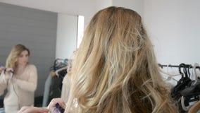 Mulher loura nova que obtém a penteado o cabelo longo com ferro no salão de beleza do cabeleireiro filme