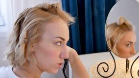 Mulher loura nova que ondula seu cabelo em tenazes de brasa, straightener cerâmico filme