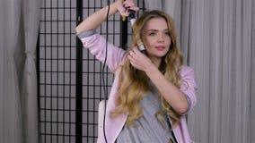 Mulher loura nova que ondula seu cabelo nos tenazes de brasa, fazendo sua denominação do cabelo filme