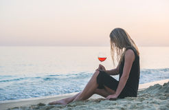 Mulher loura nova que relaxa com vidro do vinho cor-de-rosa na praia pelo mar no por do sol imagem de stock royalty free