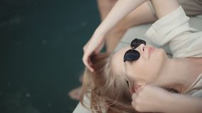 Mulher loura nova que relaxa no cais de madeira em um dia de verão filme
