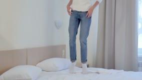 Mulher loura nova que salta na cama branca do hotel