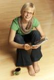 Mulher loura nova que senta-se com os pés descalços no assoalho Imagens de Stock Royalty Free