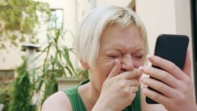 Mulher loura nova que senta-se fora e que usa o telefone foto de stock