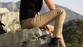 Mulher loura nova que senta-se na borda do penhasco da montanha contra o pico de montanhas bonito filme
