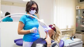 Mulher loura nova que senta-se na cadeira do dentista durante os dentes que claream o procedimento imagens de stock