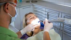 Mulher loura nova que senta-se na cadeira do dentista quando seus dentes que são treatend pelo photopolymer e pela lâmpada UV imagens de stock royalty free