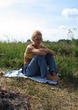 Mulher loura nova que senta-se na grama fotografia de stock royalty free