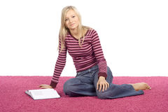 Mulher loura nova que senta-se no tapete cor-de-rosa com livro Fotografia de Stock