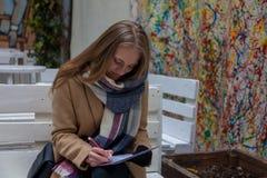 Mulher loura nova que situa no banco e na escrita imagens de stock