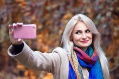 Mulher loura nova que toma o selfie no parque no outono imagem de stock