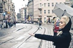 Mulher loura nova que trava o táxi na rua da cidade, menina elegante com guarda-chuva Fotos de Stock Royalty Free