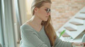 Mulher loura nova que usa o laptop ao sentar-se na tabela video estoque