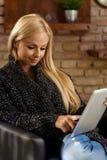 Mulher loura nova que usa a tabuleta Imagens de Stock Royalty Free