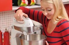 Mulher loura nova que usa um misturador na cozinha vermelha. Imagens de Stock Royalty Free