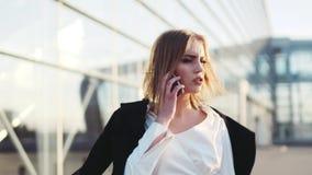 A mulher loura nova quente fala em seu telefone, verifica o tempo, toca em seu cabelo O terminal de aeroporto no fundo video estoque