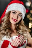 Mulher loura nova 'sexy' no traje vermelho de Santa Claus com sapatas vermelhas e o copo branco do sorriso do café do chá Fotos de Stock Royalty Free