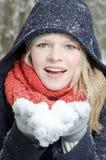 A mulher loura nova funde em um punhado da neve Imagens de Stock Royalty Free