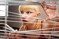 A mulher loura observa através das cortinas Foto de Stock