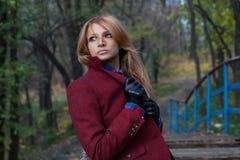 Mulher loura pensativa bonita no revestimento e nas luvas de couro mim Imagens de Stock