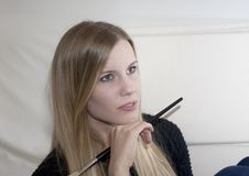 Mulher loura pensativa com escova da composição fotos de stock royalty free
