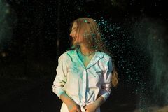 Mulher loura positiva na camisa branca que comemora o festival de Holi mim Fotos de Stock Royalty Free
