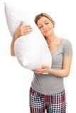 Mulher loura que abraça um descanso e um sono Imagem de Stock
