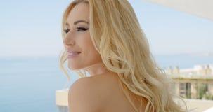 Mulher loura que admira a vista do oceano Front Balcony video estoque