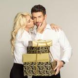 Mulher loura que beija o homem considerável com presentes fotografia de stock