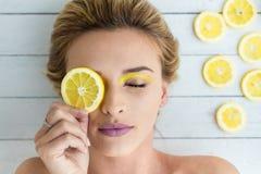 Mulher loura que coloca ao lado das fatias de limão Fotografia de Stock