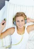 Mulher loura que encontra-se na cama quando música de escuta Foto de Stock Royalty Free