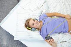Mulher loura que encontra-se na cama quando música de escuta Fotografia de Stock