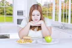 Mulher loura que escolhe o fruto ou o hamburguer da maçã Fotos de Stock