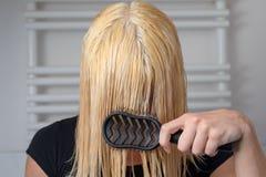 Mulher loura que escova através de seu cabelo molhado longo fotos de stock royalty free
