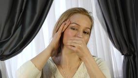 Mulher loura que faz a auto-massagem, massagem facial antienvelhecimento no escritório aptidão diária da cara e construção da car filme