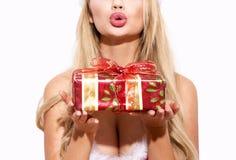 A mulher loura que guarda a caixa de presente e que envia beijos no Natal é imagem de stock