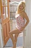 Mulher loura que inclina-se de encontro a uma porta Foto de Stock