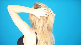 Mulher loura que joga com seu cabelo video estoque