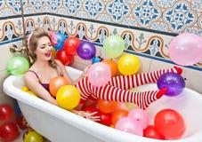 Mulher loura que joga em seu tubo do banho com os balões coloridos brilhantes Menina sensual com as meias listradas vermelhas bra Imagens de Stock