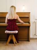Mulher loura que joga o piano em casa imagem de stock